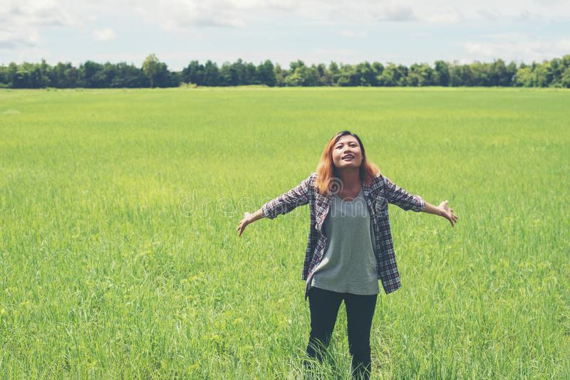Freedom Young beautiful woman stretching her arms into the sky e. Njoy and happy with fresh air at grassland stock image