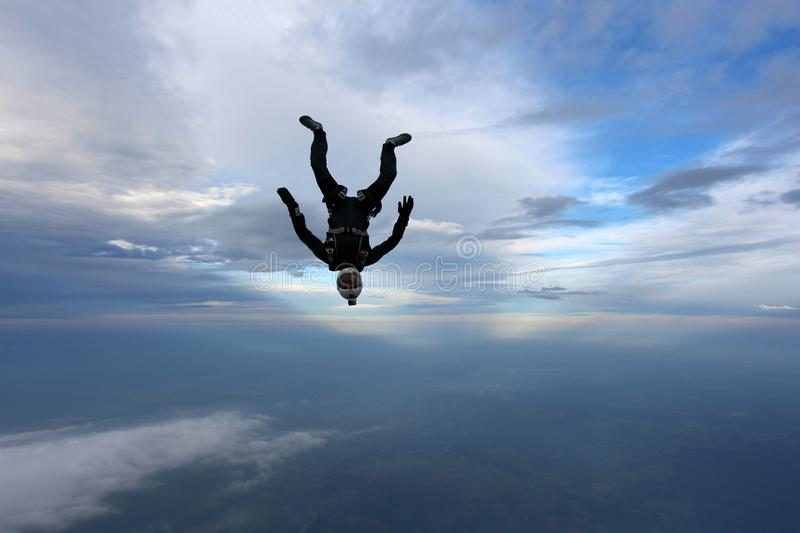 Skydiving. Skydiver is falling in head down position. stock photo