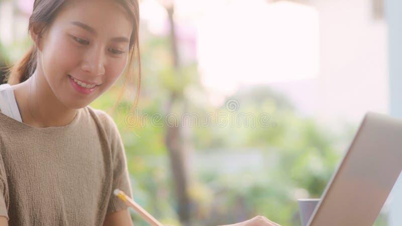 Freelance Asiatische Frau, die zuhause arbeitet, Geschäftsfrau, die am Laptop arbeitet, sitzt morgens im Garten auf dem Tisch stockbild