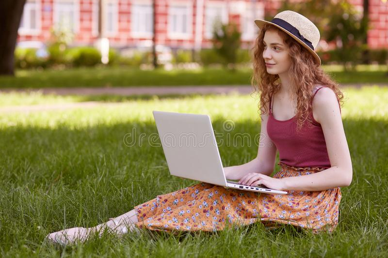 Freelance business concept. Woman sitting on green grass lawn in city park, working on laptop, has pensive facial expression, royalty free stock photos
