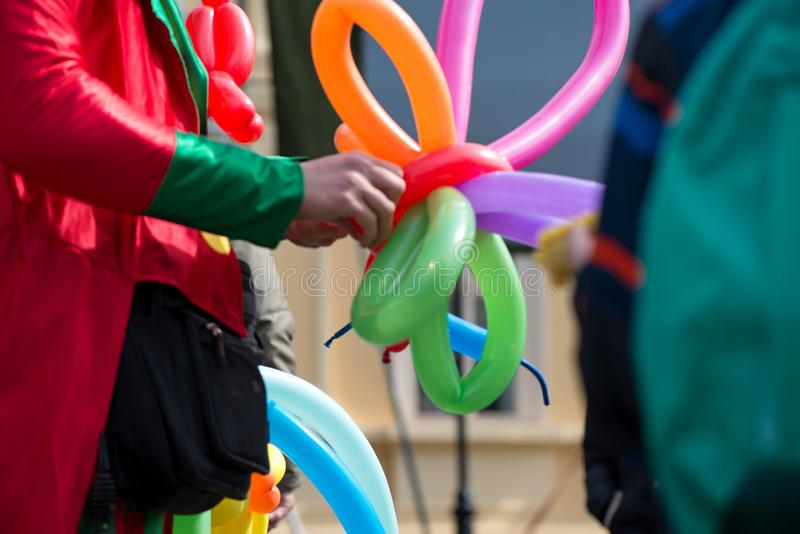 A freelance clown creating balloon animals and different shapes at outdoor festival in city center. School bag, angel wings, butterflies and dogs made of royalty free stock images