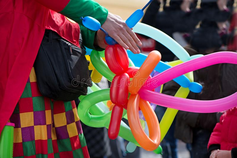A freelance clown creating balloon animals and different shapes at outdoor festival in city center. School bag, angel wings, butterflies and dogs made of stock photo