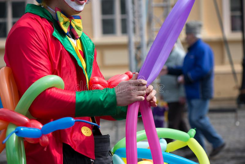 A freelance clown creating balloon animals and different shapes at outdoor festival in city center. royalty free stock photo