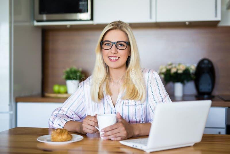 Freelance concept - vrouw in pyjama's die met laptop thuis werken stock foto