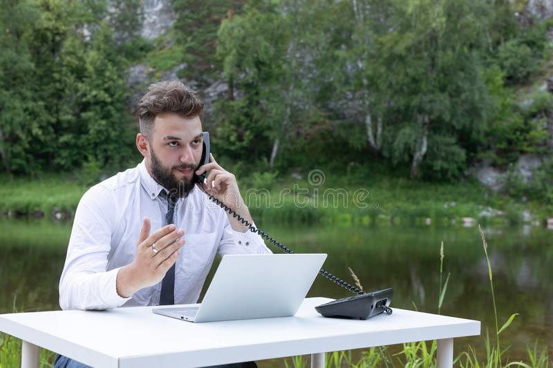 Freelance concept, work outside the office, remote work. bearded man works behind laptop in the open air. calls by phone stock images