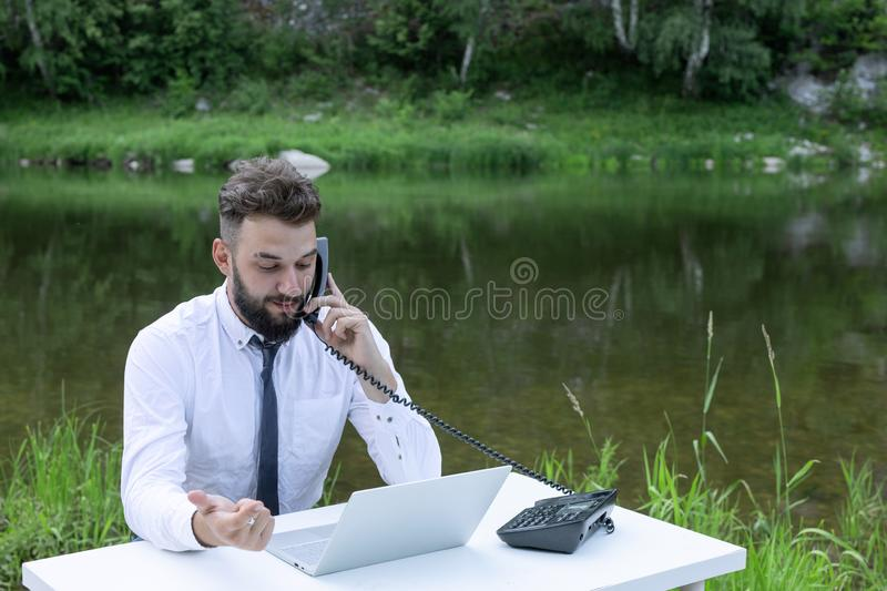 Freelance concept, work outside office, remote work. bearded man works behind laptop in the open air. calls by phone. Freelance concept, work outside the office royalty free stock images