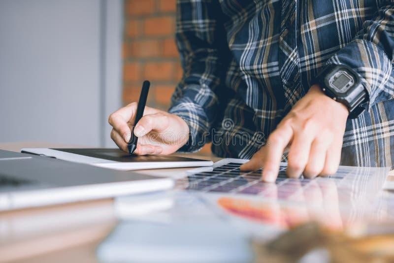 Freelance i progettisti creativi che lavorano allo scrittorio facendo uso del grafico digitale fotografia stock
