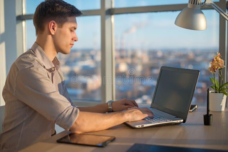 Freelance il lavoro Uomo che lavora al computer portatile immagini stock libere da diritti