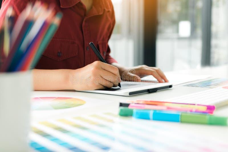 Freelance kreatywnie projektanci pracuje na biurku i rysunku z piórem używać cyfrową graficzną pastylkę w nowożytnym ministerstwi zdjęcie stock