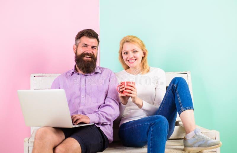 Freelance voordelen Vrouw het glimlachen het gezicht drinkt thee of koffie dichtbij man het werken Het meisje geniet van drank te stock foto's