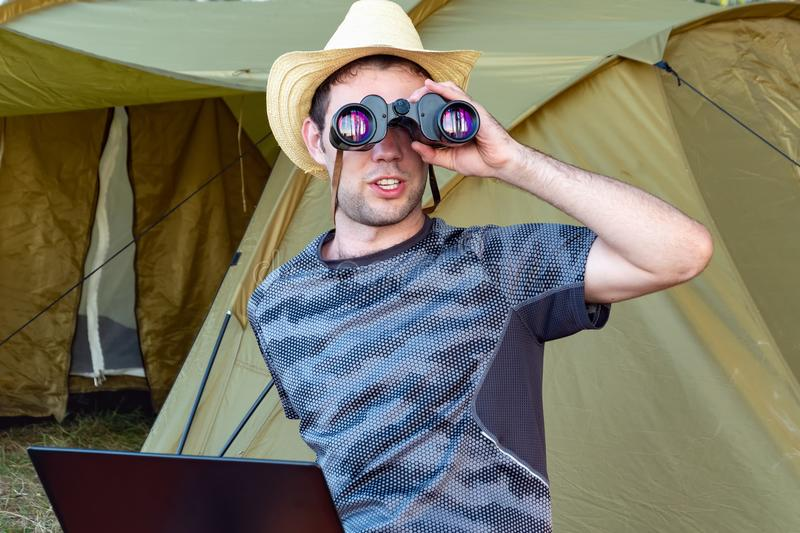 A young man in a hat sitting with a laptop near the tent and looks through binoculars royalty free stock photo