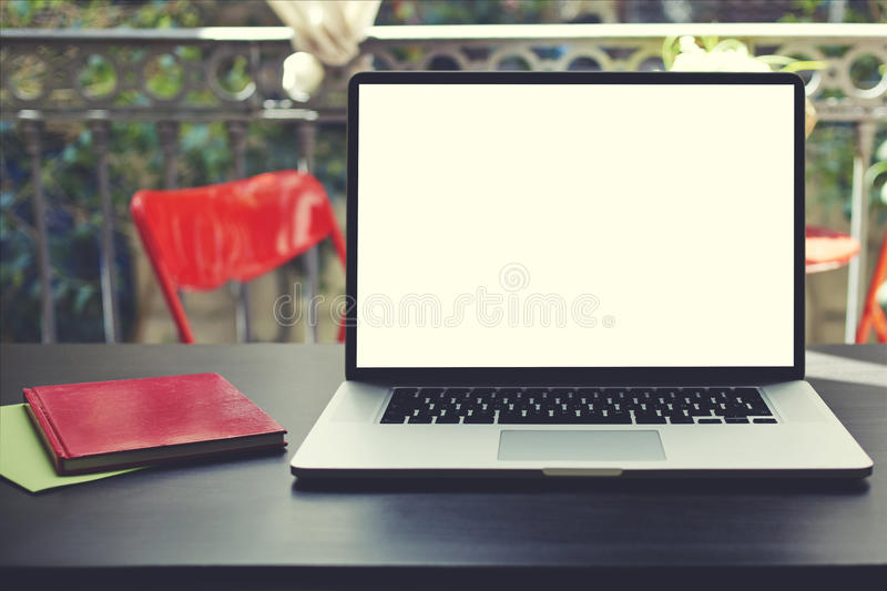 Freelance workplace with empty display notebook on modern table in home interior. Laptop computer with blank copy space screen for your information or content royalty free stock image