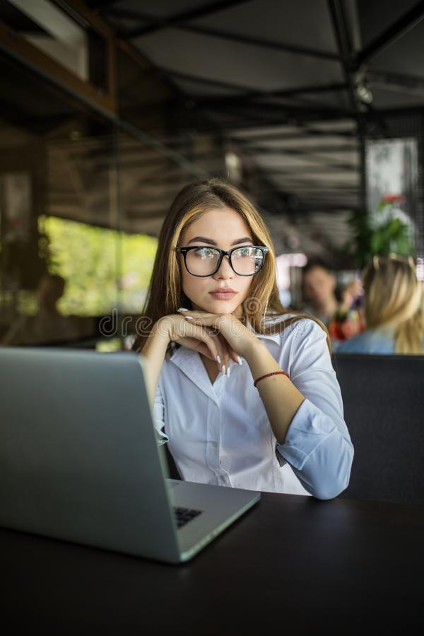 Freelance young woman sitting in the cafeteria with laptop. And drinking coffee stock photos