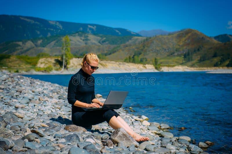 Freelancer με το lap-top στη φύση Εργασίες γυναικείων όμορφες κοριτσιών ταξιδι στοκ φωτογραφία με δικαίωμα ελεύθερης χρήσης