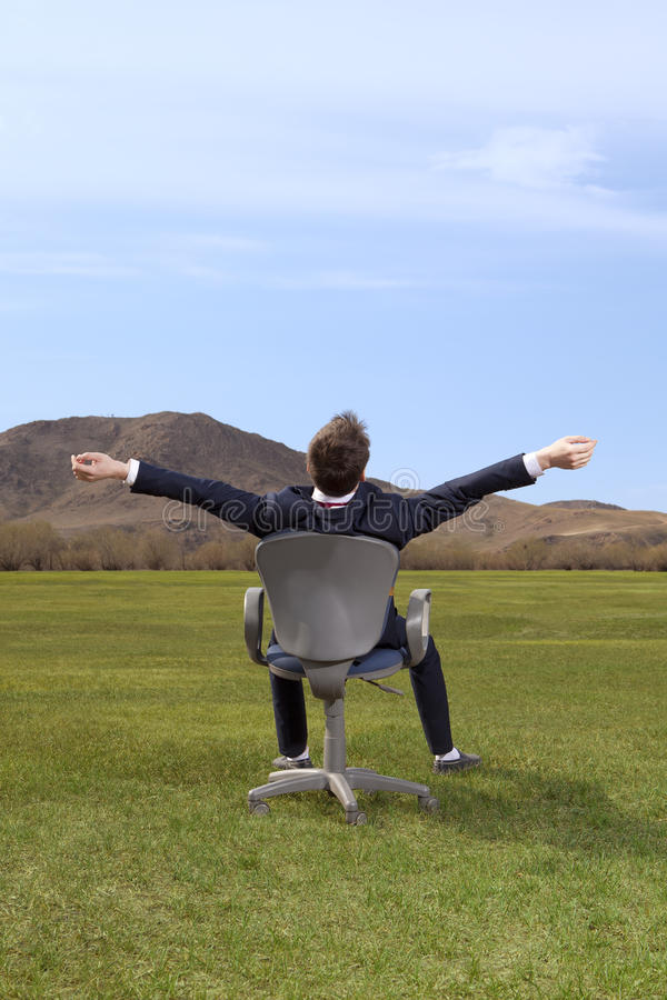 freelancer Бизнесмен сидя на стуле на зеленом луге стоковая фотография rf