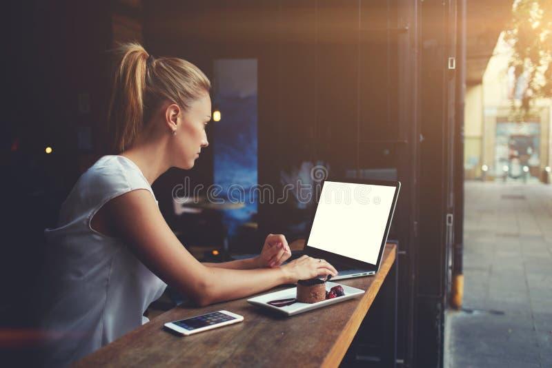 Freelancer acertado de la mujer linda que usa el ordenador portátil mientras que se sienta en cafetería fotos de archivo