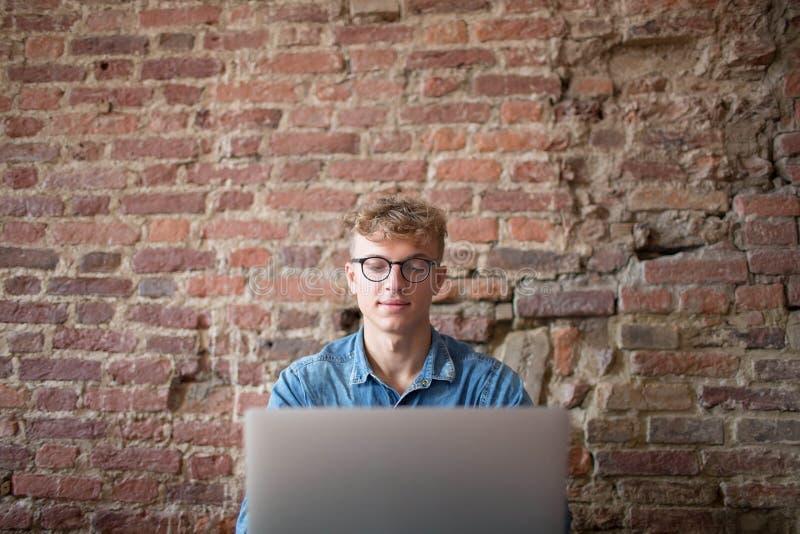 Freelancer acertado del hombre joven que usa el ordenador portátil para el trabajo en Internet, sentándose en espacio de co-traba imagen de archivo
