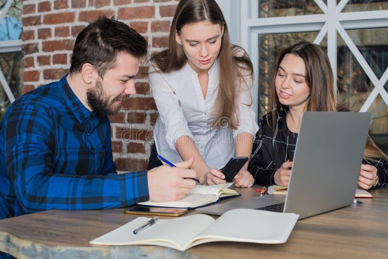 Freelancer acertado del trabajo en equipo, usando el teléfono de célula y el red-libro moderno Partners la colaboración imágenes de archivo libres de regalías