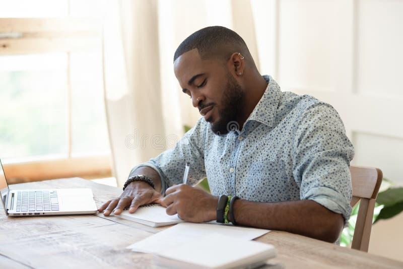 Freelancer africano enfocado del estudiante del hombre que hace las notas que estudian con el ordenador portátil fotos de archivo
