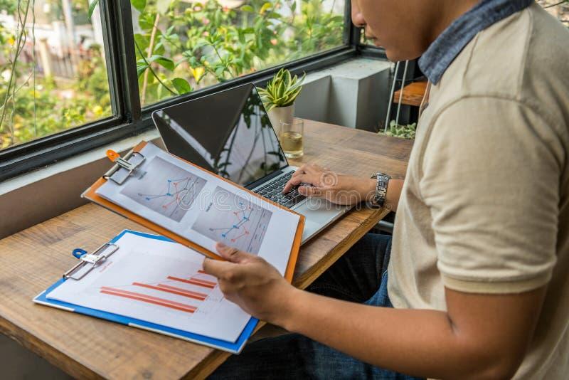 Freelancer asiático que trabalha com portátil, documentos no escritório verde fotos de stock royalty free