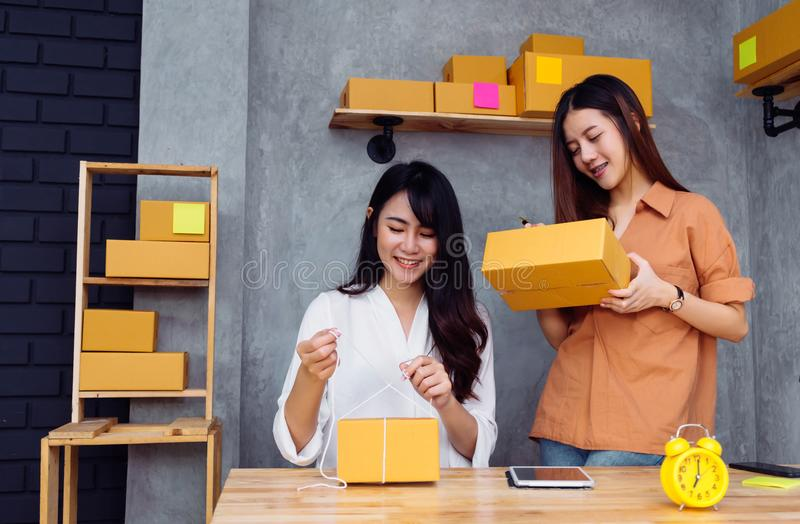 Freelancer asian women teamwork sme business. Working at office in home interior writing address,packing order for customer and online delivery for ready stock photos