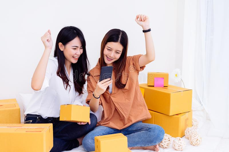 Freelancer asian women teamwork sme business working. At office in home interior packing order for customer and online delivery for ready packing on living room stock photos