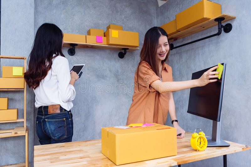 Freelancer asian women teamwork sme business. Working at office in home interior writing address order for customer and online delivery for ready packing on stock photos