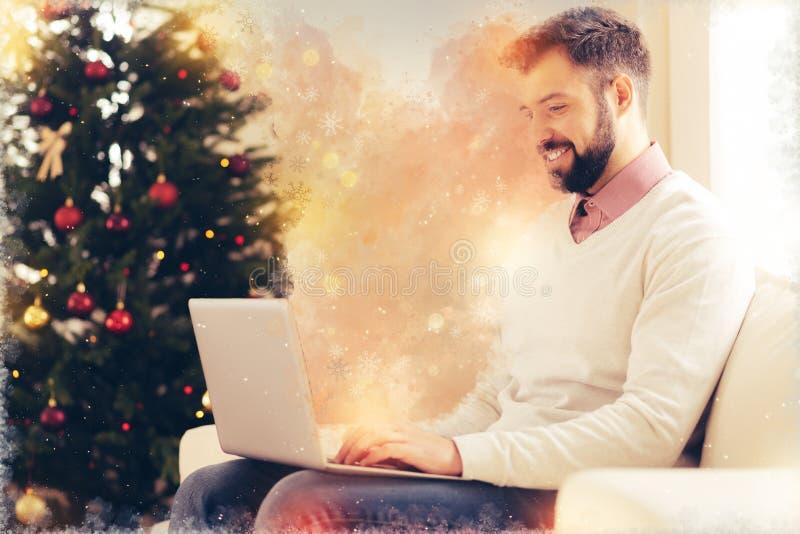 Freelancer barbudo hermoso que trabaja en casa sentarse cerca del árbol de navidad imagen de archivo libre de regalías