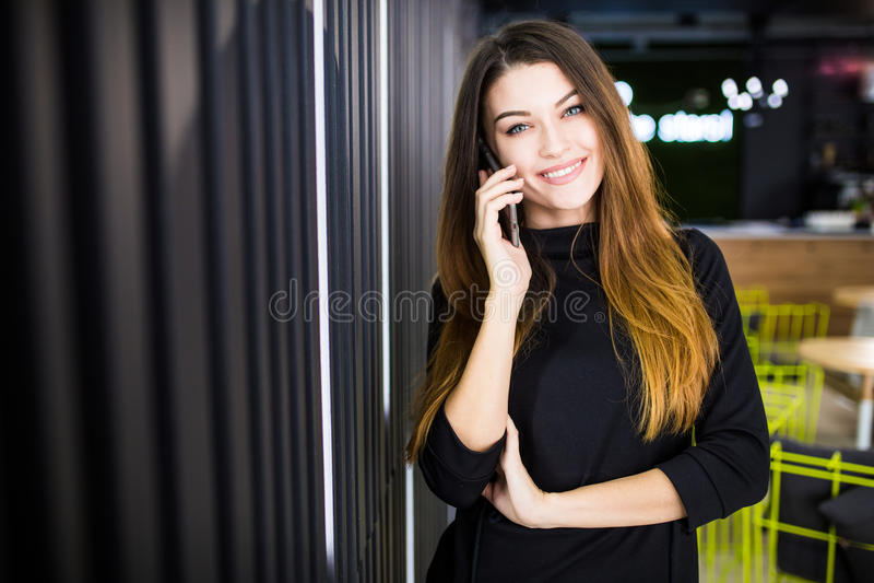 Freelancer biznesowa kobieta opowiada na telefonie komórkowym z biurowym pokojem w tle obraz royalty free