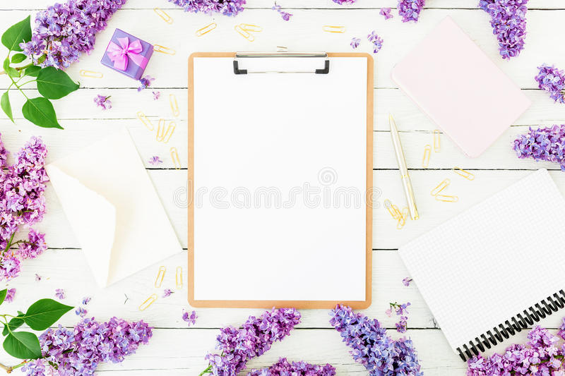 Freelancer or blogger concept. Minimalistic workspace with clipboard, envelope, pen, box, lilac and accessories on white backgroun stock image