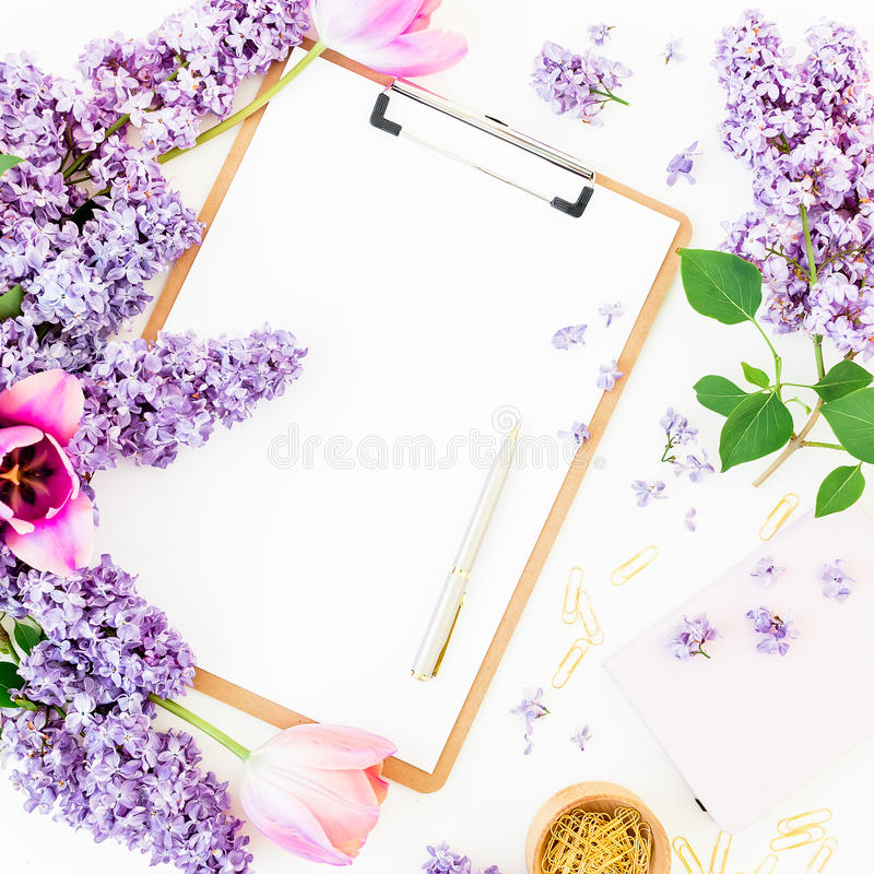 Freelancer or blogger workspace with clipboard, notebook, pen, lilac, and tulips on white background. Flat lay, top view. stock photos