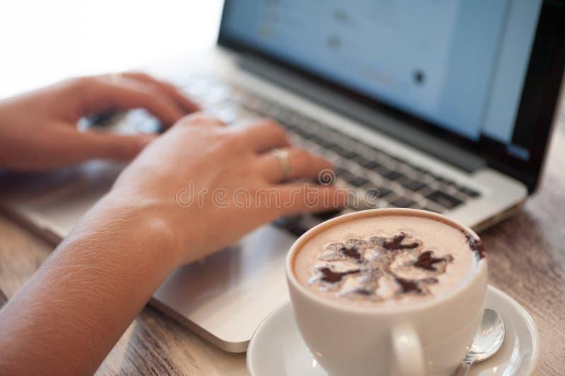 Freelancer da jovem mulher que datilografa no portátil no café imagem de stock