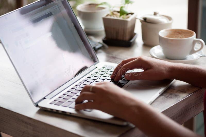 Freelancer da jovem mulher que datilografa no portátil no café imagens de stock