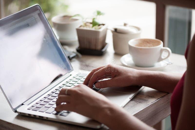 Freelancer da jovem mulher que datilografa no portátil no café fotografia de stock