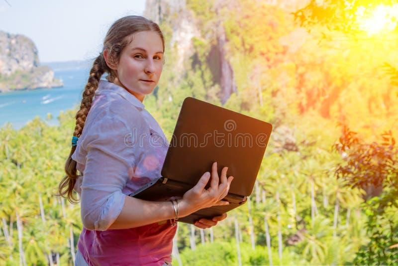 Freelancer da jovem mulher que trabalha com port?til em uma parte superior da montanha com vista no mar e na praia tropical Traba imagens de stock