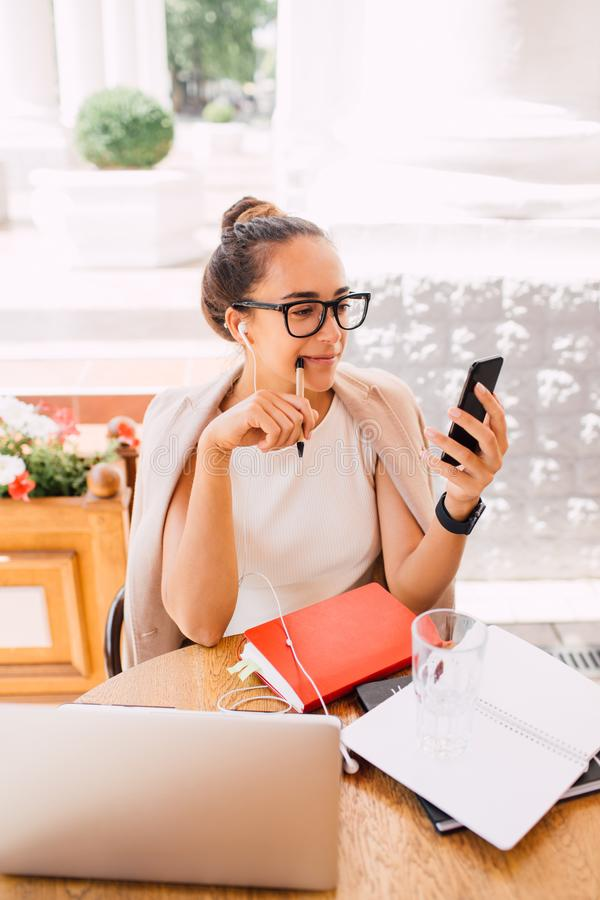 Freelancer da jovem mulher que usa o portátil e o smartphone no café da rua fotos de stock