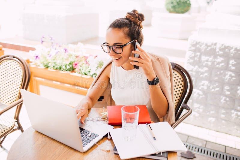 Freelancer da jovem mulher que usa o portátil e o smartphone no café da rua imagens de stock royalty free