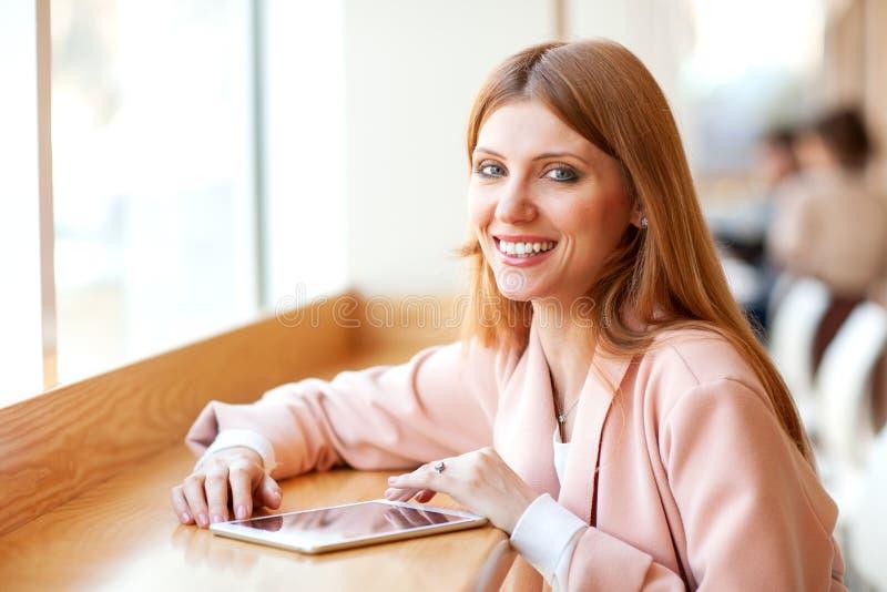 Freelancer de la muchacha que sostiene una tableta en el caf? foto de archivo libre de regalías