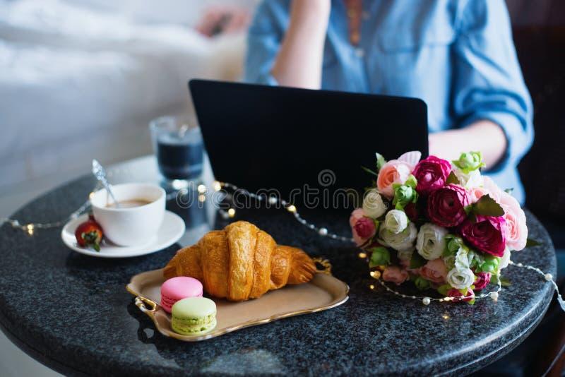 Freelancer de la mujer joven en el funcionamiento azul de la camisa en el ordenador portátil durante almuerzo con café, el cruasá foto de archivo