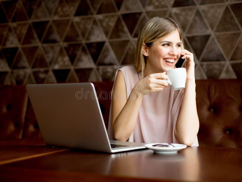 Freelancer de la mujer que trabaja en el ordenador portátil en café y café de consumición imagen de archivo libre de regalías