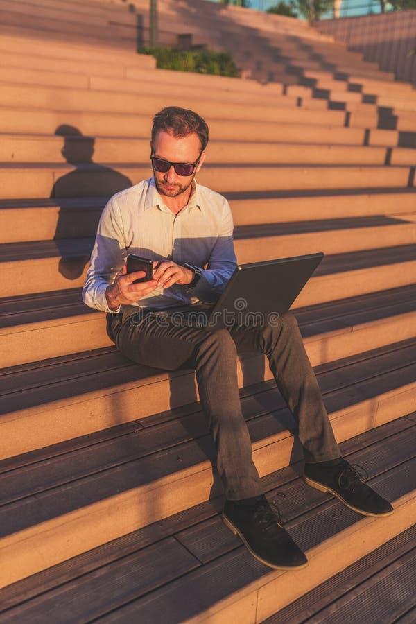 Freelancer de moda que usa smartphone y el ordenador portátil mientras que se sienta en las escaleras durante puesta del sol imagenes de archivo