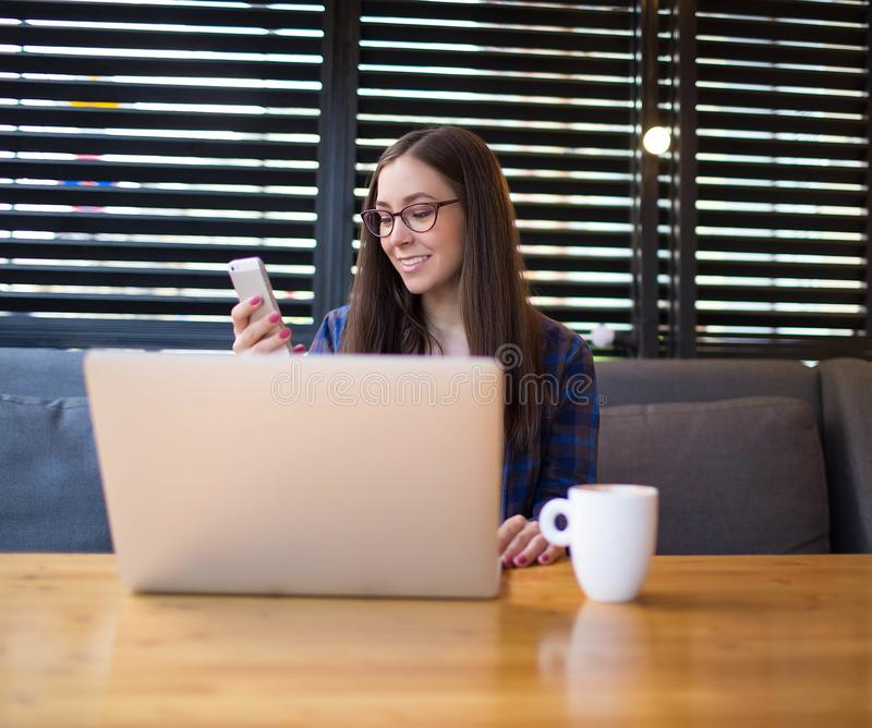 Freelancer de sexo femenino alegre que tiene llamada video en el teléfono de célula fotos de archivo libres de regalías