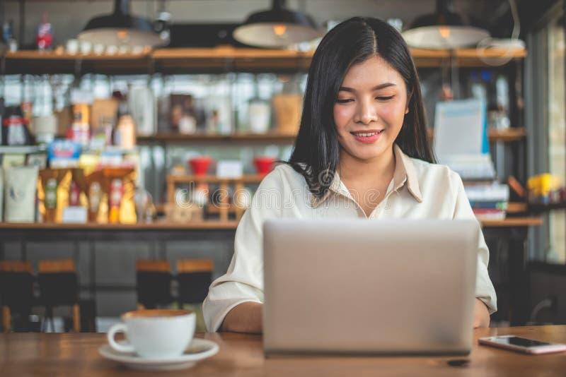 Freelancer de sexo femenino asiático que sonríe cuando usando el ordenador portátil en café Concepto del negocio y del éxito Tema imagen de archivo libre de regalías