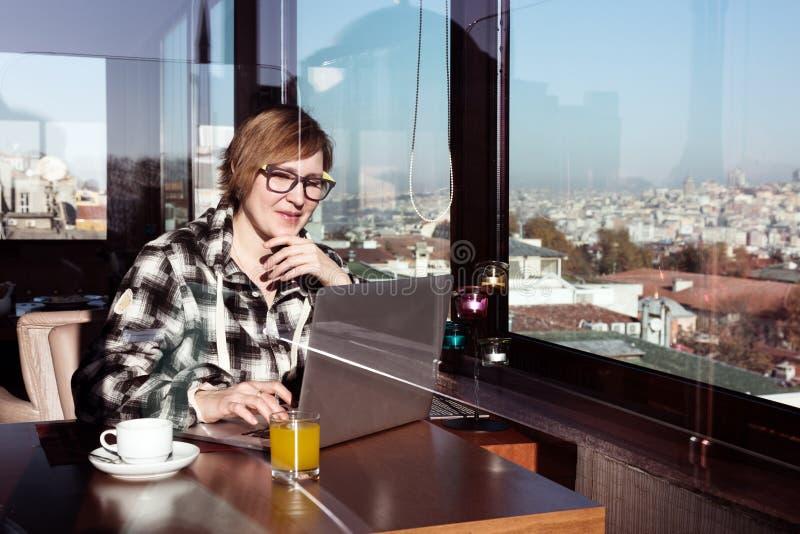 Freelancer de sexo femenino sonriente que trabaja en el ordenador en el café del top del tejado imagen de archivo
