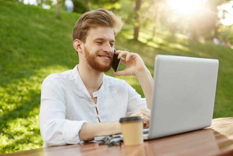 Freelancer de sexo masculino del pelirrojo hermoso joven con buen corte de pelo y barba, trabajando en el ordenador portátil en e imagen de archivo