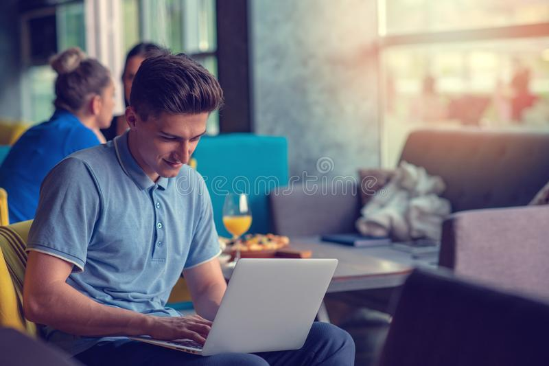 Freelancer de sexo masculino experto joven que comienza día laborable temprano en el café de consumición de la mañana a despertar imagen de archivo
