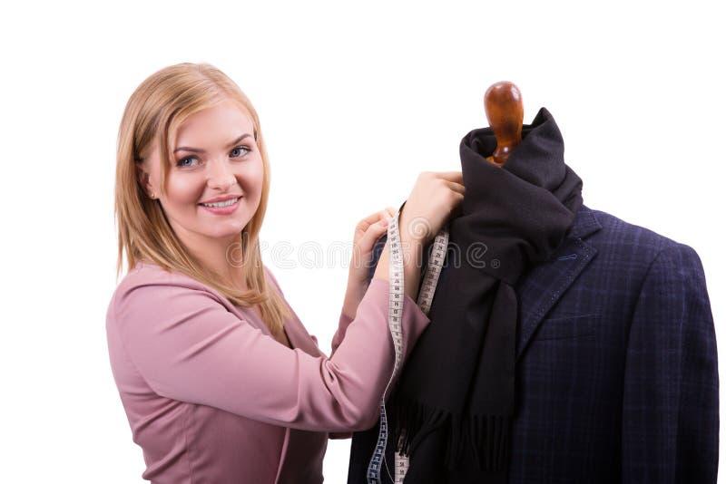 Freelancer - den modeformgivaren eller skräddaren som arbetar på en design eller ett utkast, tar hon måttet på falska sömmerskor arkivbilder