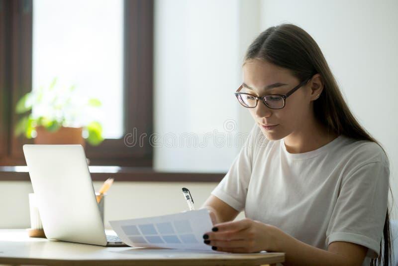 Freelancer die bij laptop werken die informatie neerschrijven stock fotografie