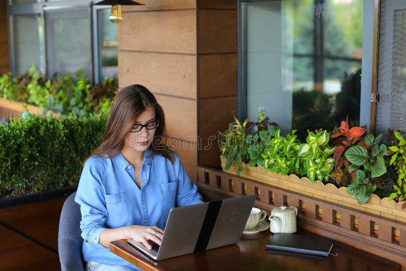 Freelancer die door smartphone spreken en met laptop bij koffie werken stock foto