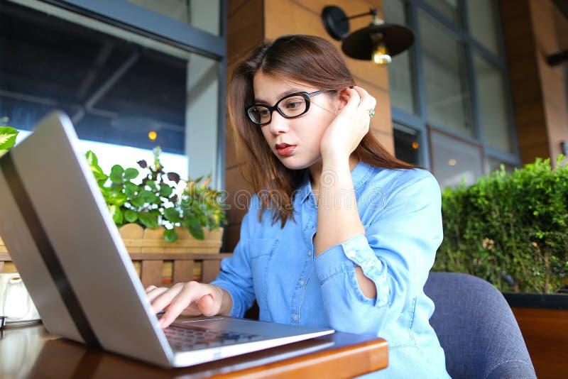 Freelancer die door smartphone spreken en met laptop bij koffie werken stock fotografie
